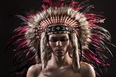 stock photo of headdress  - Portrait of the naked indian strong man posing with traditional native american make up  and headdress looking at the camera - JPG