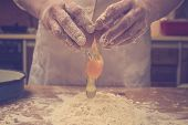 image of confectioners  - Closeup photo of baker cracking egg for dough - JPG
