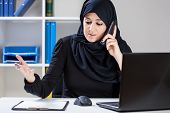 foto of muslim  - Muslim businesswoman during work in the office - JPG