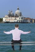 image of girder  - Businessman sitting on light metal girder beam Venice Italy in background - JPG