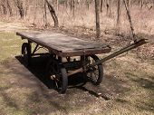 stock photo of wagon  - Utilitarian flat bed wooden wagon updated just a bit with rubberized wheels to make it functional - JPG