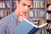stock photo of concentration man  - Concentrated young man reading book and holding hand on chin while standing against bookshelf - JPG