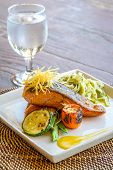 stock photo of salmon steak  - grilled salmon steak served with pasta and vegetables in a small outdoor restaurant - JPG