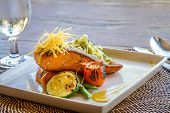 stock photo of pasta  - grilled salmon steak served with pasta and vegetables in a small outdoor restaurant - JPG