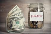picture of emergency light  - Dollars and coins in glass jar with emergency label - JPG