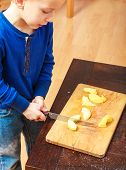 image of unawares  - Child little boy playing dangerous game with a kitchen knife cut apple making salad at home - JPG