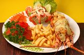 stock photo of lobster  - Lobster thermidor baked lobster served with shrimp cocktail and French fries - JPG