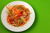picture of green papaya salad  - thai hot papaya salad with a green background - JPG