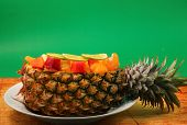 stock photo of green papaya salad  - Thai style fruit salad inside a pineapple with a green background on a wood table top - JPG