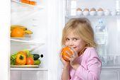 foto of refrigerator  - Little cute girl looking at camera and holding orange near open fridge - JPG