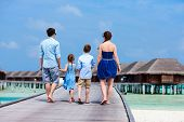 image of jetties  - Back view of happy beautiful family walking on wooden jetty during summer vacation at luxury resort - JPG