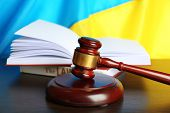 picture of proceed  - Wooden gavel and flag of Ukraine as background - JPG