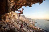 foto of cave woman  - Young woman lead climbing in cave with beautiful view in background - JPG