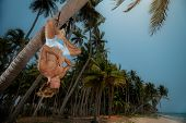 foto of upside  - Muscular man doing upside down yoga on palm tree - JPG