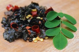 picture of malunggay  - Fried and moringa leaves on wooden surface - JPG