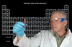 picture of periodic table elements  - Scientist studying a vial of chemical in front of a Periodic table of Elements - JPG