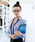 pic of secretary  - Portrait of pretty young secretary holding folders - JPG