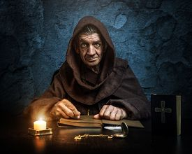 picture of priest  - Priest hood by candlelight reading the Bible - JPG