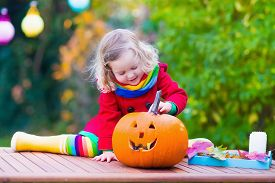 picture of carving  - Little girl carving pumpkin at Halloween - JPG