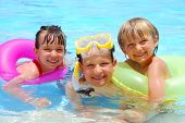 stock photo of swimming pool family  - Three happy children in a swimming pool - JPG