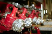 stock photo of fire truck  - Fireman fire truck hose faucets in a row red and silver - JPG