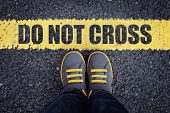 Do not cross line child in sneakers standing next to a yellow line with restriction or safety warnin poster