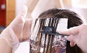 Process of dyeing hair at beauty salon, closeup poster