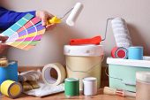 Painting Tools For Home On Parquet With White Wall Background And Painter Choosing Colors On A Color poster