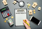 Table With Wooden Houses, Calculator, Coins, Magnifying Glass With The Word Property Investments. At poster