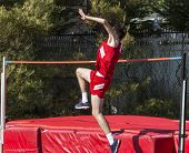 A High School Track And Field High Jumper Is Taking Off From The Ground As He Attempts To Jump Over  poster
