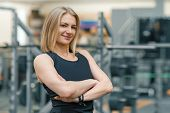 Portrait Of Adult Blonde Fitness Woman Personal Trainer With Folded Hands In The Gym, Beautiful Smil poster