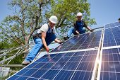 Two Young Technicians Installing Heavy Solar Photo Voltaic Panel On Tall Steel Platform On Green Tre poster