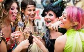 Happy girls at Carnival parade clinking glasses with champagne poster