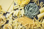 Background Texture From Variety Of Types And Shapes Of Italian Pasta On Old Wooden Background From A poster