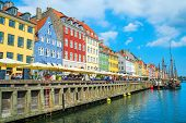 Tourists On Nyhavn Embankment With Cafes And Restaurants In Bright Sunny Day, Boats Sailing By Canal poster