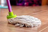 Rope Mop For Cleaning The Floor Is On The Floor Of The Tile. poster