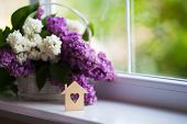 Wooden House With Hole In Form Of Heart And Tender Bouquet Of Beautiful Lilac In White Basket Near W poster