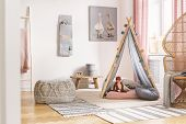 Patterned Pouf On Carpet Next To Tent With Cushions In White Kids Room Interior With Poster. Real P poster