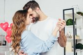Selective Focus Of Tenderly Smiling Couple Dancing On St Valentine Day At Home poster