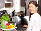 Woman Using Laptop Computer In Kitchen
