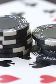 stock photo of slot-machine  - two stacks of black poker chips on cards - JPG