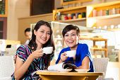 Asian female friends enjoying her leisure time in a cafe, drinking coffee or cappuccino and talking