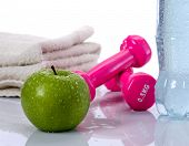 Towel, water, apple, dumbells lying isolated on white