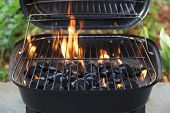 stock photo of charcoal  - charcoal grill with flames at garden barbeque party close up - JPG