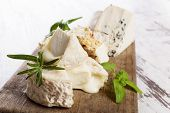 stock photo of brie cheese  - Luxurious goat cheese variation and blue cheese on wooden kitchen board on white wooden background. Luxurious cheese still life.