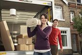 pic of moving van  - Portrait of happy young couple carrying rolled carpet by moving van - JPG