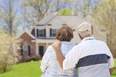 stock photo of yard sale  - Happy Senior Couple From Behind Looking at Front of House - JPG