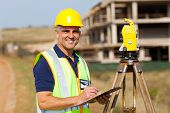stock photo of theodolite  - happy senior land surveyor at work - JPG