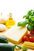 Piece of gouda cheese with pasta ingredients including tomatoes, basil leaves, zucchinis, olive oil,