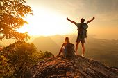 stock photo of sunrise  - Two hikers enjoying sunrise from top of a mountain - JPG
